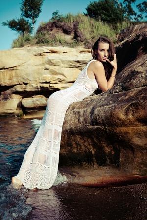 Beautiful female model poses in sand rocks