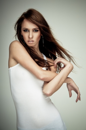 Young brunette lady posing on grey background photo