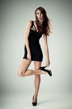 wind dress: Young brunette lady in black dress posing on grey background Stock Photo