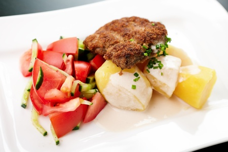 Minced meat cutlet with boiled potatoes and tomato-cucumber salad photo