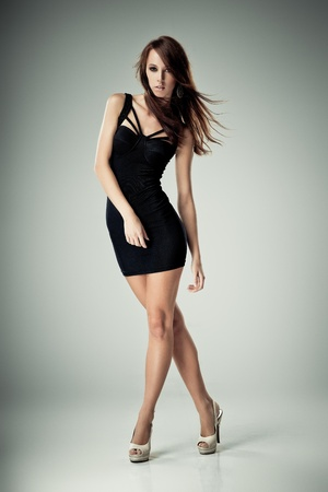 Young brunette lady in black dress posing on grey background photo
