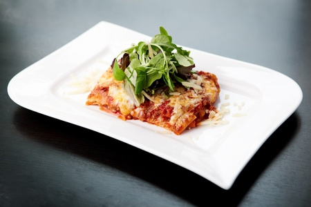 Lasagna served on a white plate with salad photo