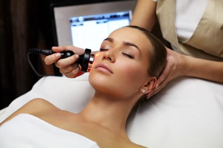 Woman lies on a table in a beauty spa getting a treatment photo