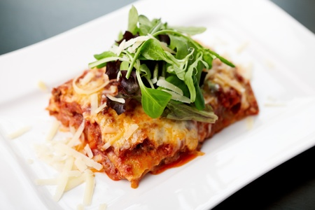 lasagna: Lasagna served on a white plate with salad