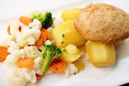 Chicken Kiev with cauliflower, carrot and broccoli. photo
