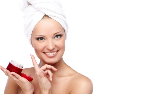 Young beautiful lady with a towel on her head applying creme photo