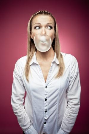 goma de mascar: Mujer joven que hace una burbuja de chicle y mirando a la derecha