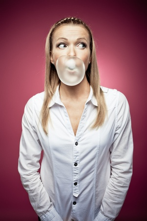 gums: Young woman making a chewing gum bubble and looking right
