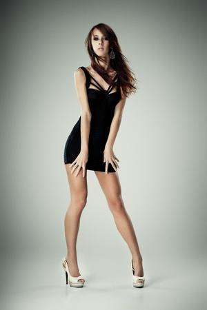 Jeune femme brune en robe noire posant sur fond gris Banque d'images