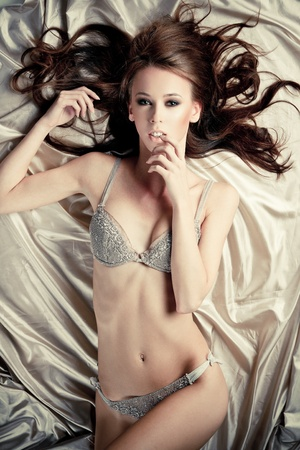 Beautiful lady in lingerie lying in bed of silk sheets Stock Photo - 11408439