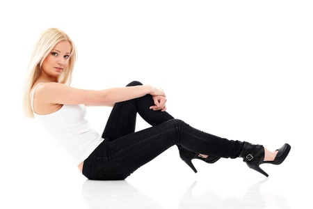 Smiling sexy blond woman in white shirt and  jeans sitting on a floor isolated on white photo