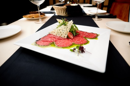 Beef carpaccio with salad and Parmesan cheese photo