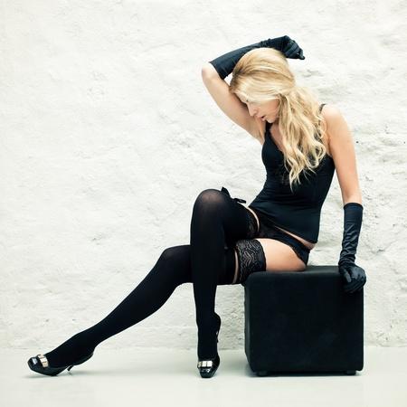 Blond lady in black lingerie sitting near a wall Banco de Imagens