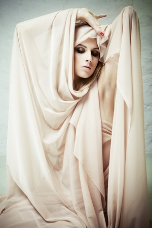 A woman trying to get out of the cocoon of beige fabrics photo