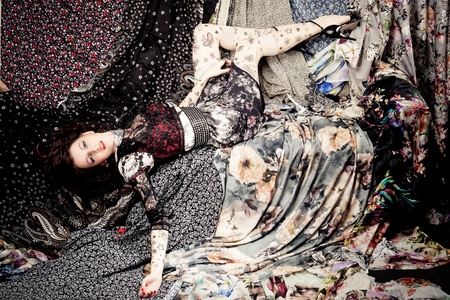 Woman lying on a pieces of colorful fabrics photo