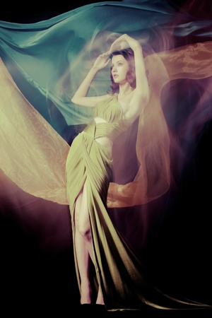 Fashion portrait of brunette lady in long dress shot in mixed light technique photo