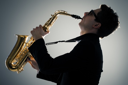 playing music: Young man playing sax in the dark