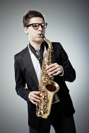 Young man playing sax on gray background