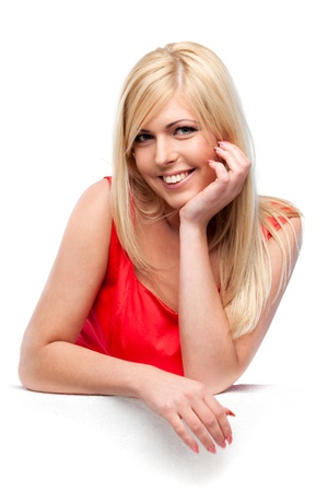 female elbow: Portrait of blond lady in a red dress leaning on white surface Stock Photo