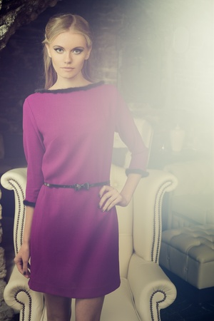 Young blond lady in lilac dress posing in vintage interior photo