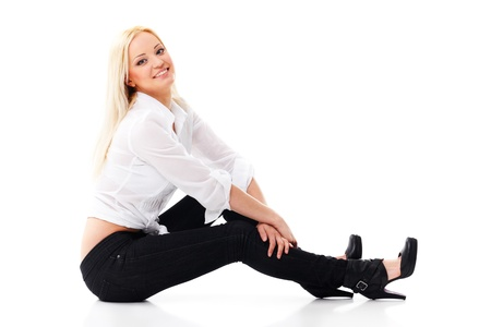 hot legs: Smiling sexy blond woman in white shirt and  jeans sitting on a floor isolated on white