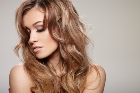 Young brunette lady with a beautiful hair on gray background Stock Photo