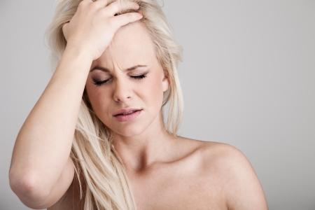 femme triste: Portrait d'une jeune femme souffrant de maux de t�te sur fond Banque d'images