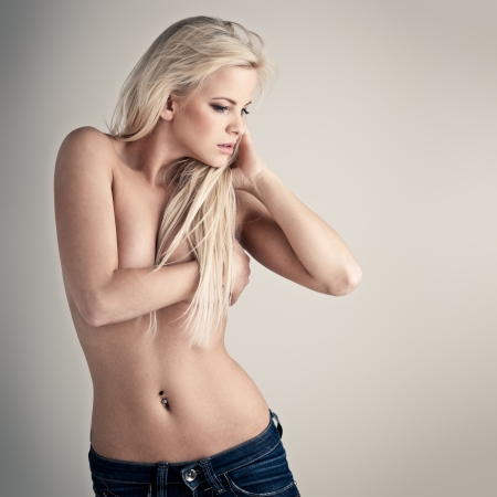 Young topless lady in blue jeans on gray background photo