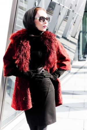 Stylish lady in bright red coat in a city scene photo