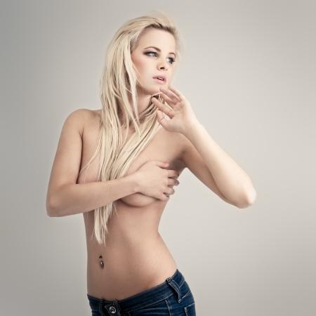 seins nus: Jeune femme topless dans blue jeans sur fond gris Banque d'images