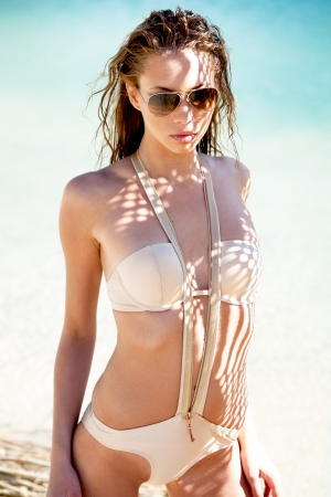 Young woman on a beach in bikini and sunglasses