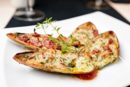 Baked mussels with parmigiano cheese and white wine in tomato coolie photo