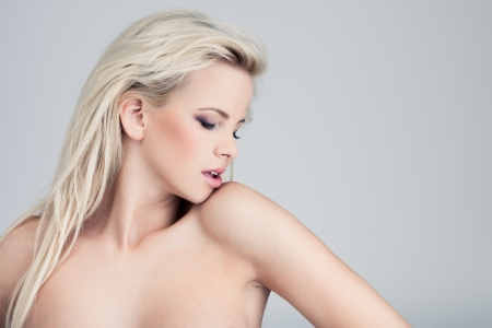nude girl pretty young: Young blond lady with a beautiful hair on gray background
