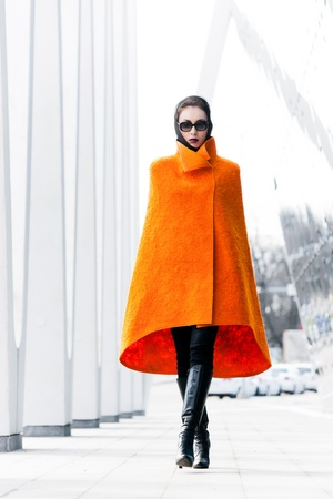 street fashion: Stylish lady in bright orange coat in a city scene Stock Photo