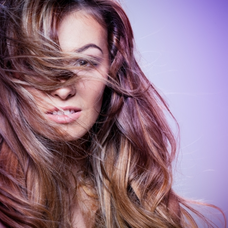 ringlet: Young brunette lady with a beautiful hair on gray background Stock Photo