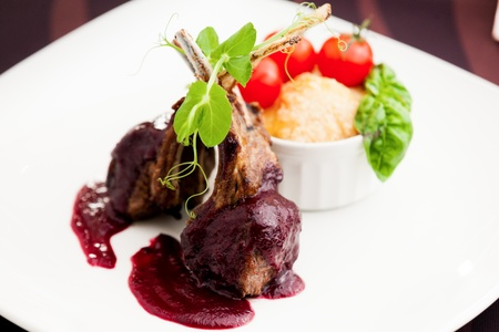 Grilled lamb served with cranberry sauce  tomatoes and potato garnish photo