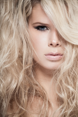 Closeup portrait of a blond lady with hair over her face photo