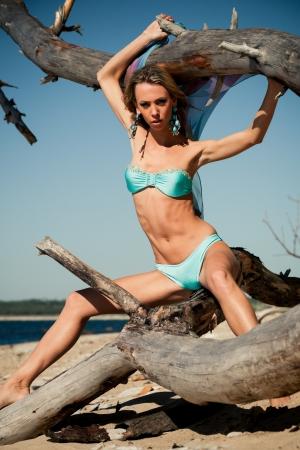 snag: Young woman in bikini posing near a snag on a beach Stock Photo