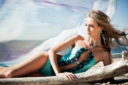 hot lady: Young woman in bikini posing near a snag on a beach Stock Photo