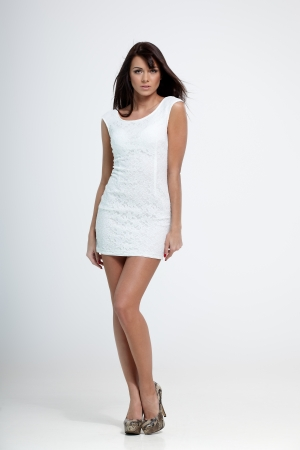 transparent dress: Young beautiful female model in white dress on gray background