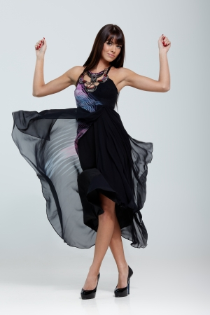 Fashionable lady in black dress posing on gray background photo