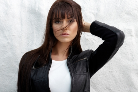 Glamorous young woman in black leather jacket posing near white wall Stock Photo - 16695343