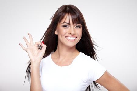 ��smiling: Joven linda chica sonriente que muestra signo de OK sobre fondo gris