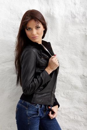 Glamorous junge Frau in der schwarzen Lederjacke posiert in der Nähe weiße Wand Standard-Bild - 16796437