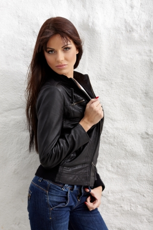 Glamorous young woman in black leather jacket posing near white wall