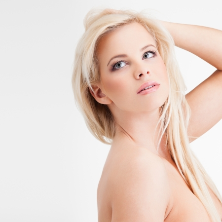 Portrait of a sensual young blond woman on gray background photo