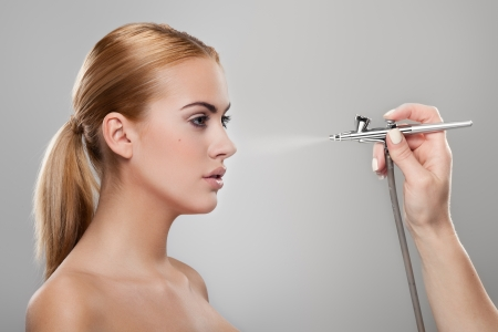 Make-up artist spraying foundation on a model s face photo
