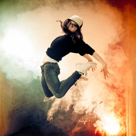 hip hop dancing: Teenage brakedancer girl jumping in a smoke