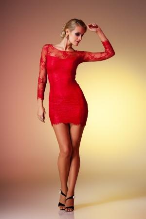 tacones negros: Jovencita morena con vestido rojo posando sobre fondo de colores