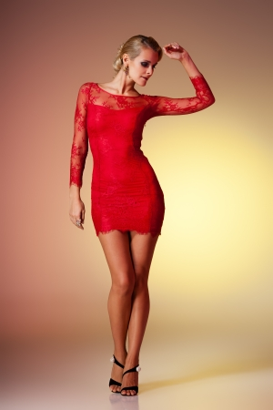 Young brunette lady in red dress posing on colorful background photo